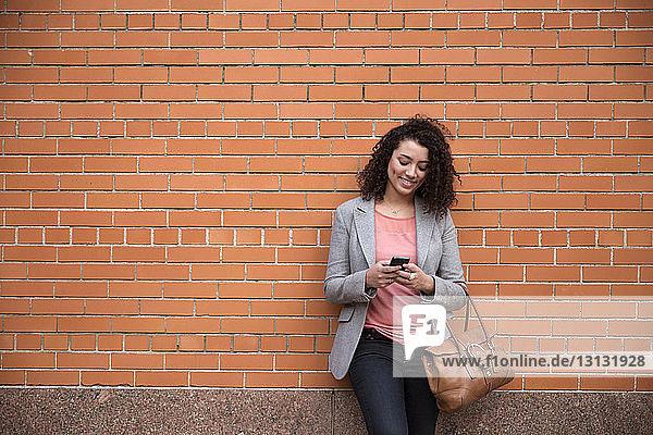 Lächelnde Geschäftsfrau benutzt Smartphone  während sie an einer Ziegelmauer steht