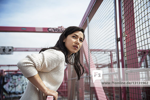 Side view of young woman looking away while standing on Williamsburg bridge