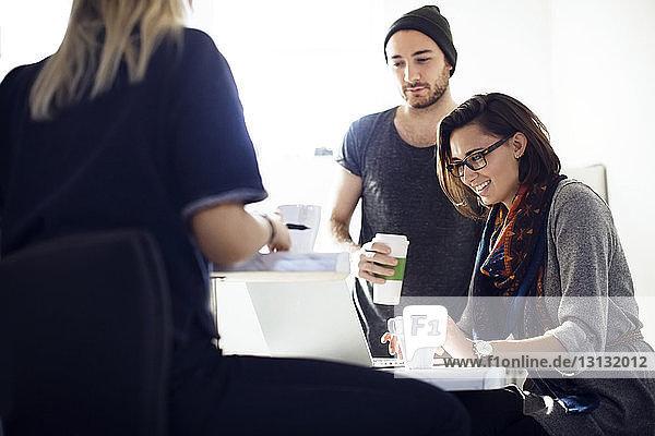 Geschäftsleute diskutieren in der Kaffeepause im Büro