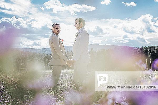 Homosexuelles Paar hält sich an den Händen  während es auf dem Feld vor bewölktem Himmel steht
