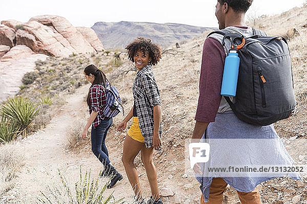 Freunde wandern auf Felsformationen bei klarem Himmel