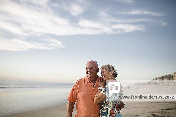 Lächelndes älteres Paar  das bei Sonnenuntergang am Strand gegen den Himmel steht