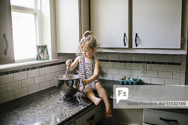Girl preparing food in container while sitting on kitchen counter at home