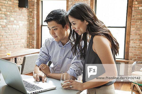 Ehemann und Ehefrau benutzen zu Hause einen Laptop