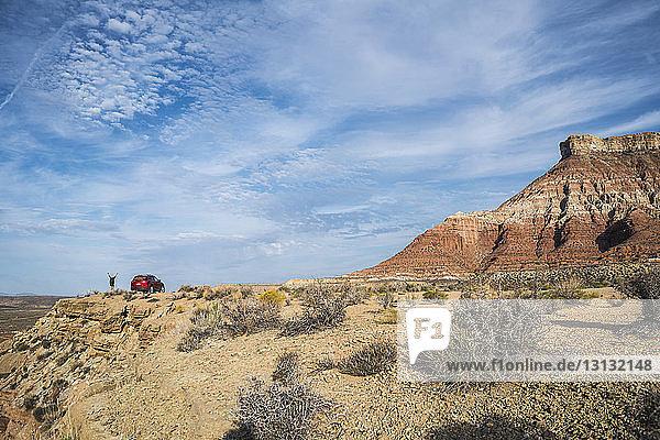Fernansicht einer Frau  die am Auto auf einem Berg gegen den Himmel steht