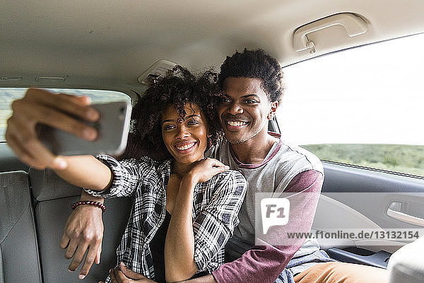 Happy couple taking selfie while traveling in car