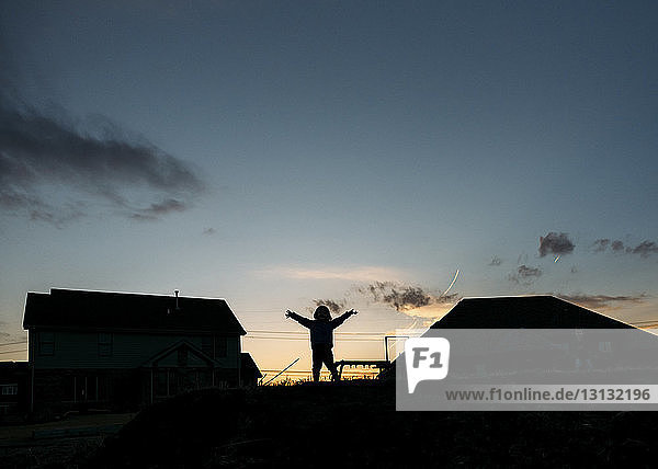 Silhouette of boy standing in backyard against sky