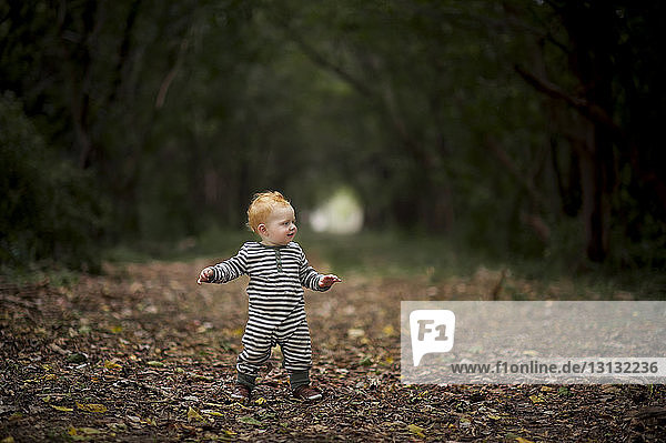 Cute baby boy looking away while standing at park
