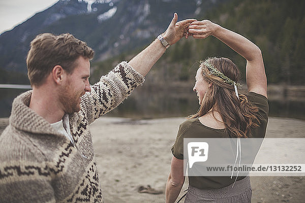 Happy young couple dancing on lakeshore at Silver Lake Provincial Park