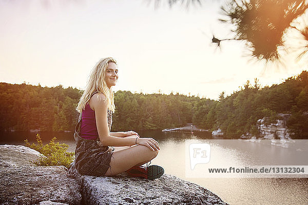 Side view portrait of young woman sitting on rock by lake against sky
