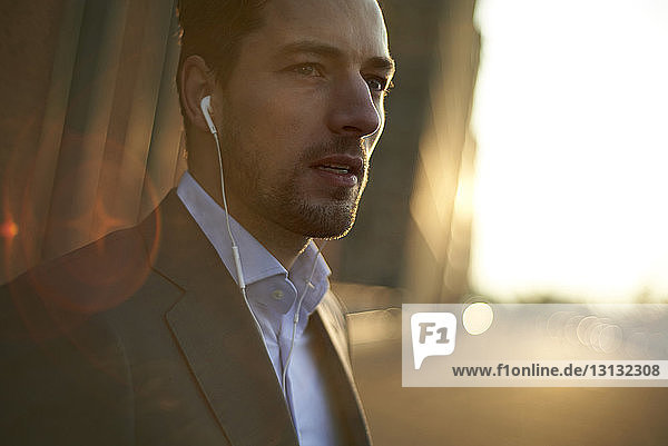 Confident businessman listening music while standing outdoors