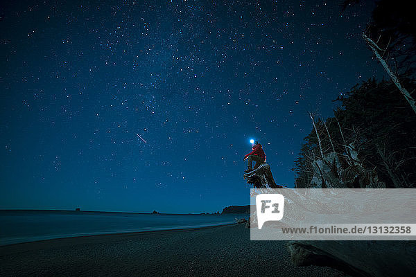 Hiker wearing headlamp sitting on tree trunk at La Push beach against star field