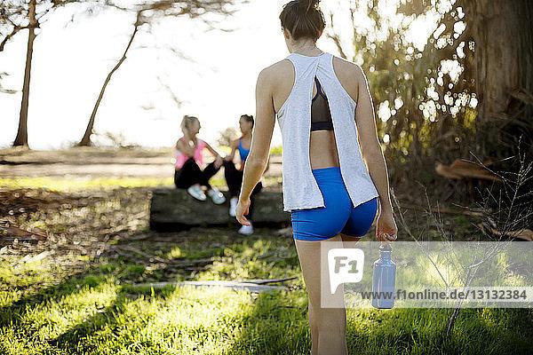 Rückansicht einer Frau  die auf Freunde auf dem Feld zugeht