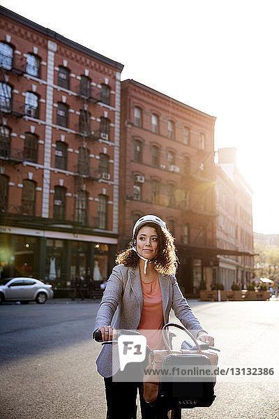 Nachdenkliche Geschäftsfrau hält Fahrrad auf Straße