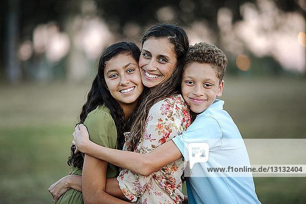 Porträt einer liebenden Mutter und Kinder  die sich im Park umarmen