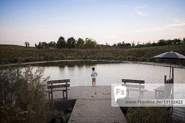 High angle view of boy standing on pier over lake at park