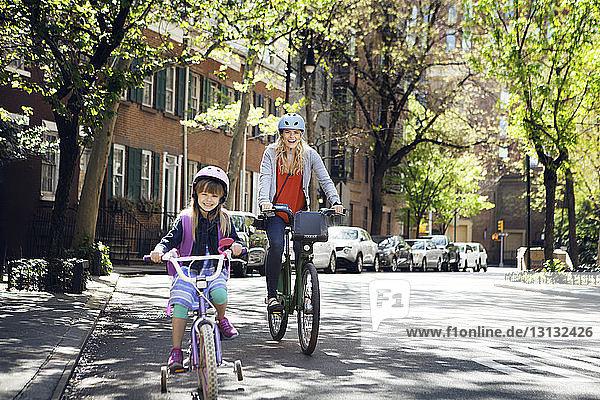 Porträt einer fröhlichen Mutter und Tochter beim Fahrradfahren auf der Straße