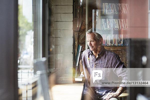 Lächelnder reifer Mann am Tisch sitzend durch Glas im Café gesehen