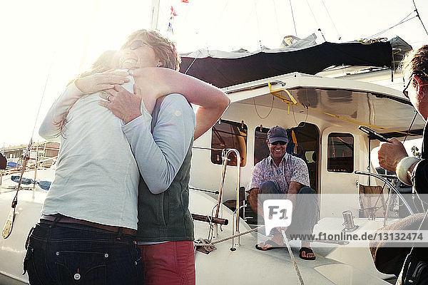 Frauen umarmen sich  während ein Mann ein Seil im Boot hält