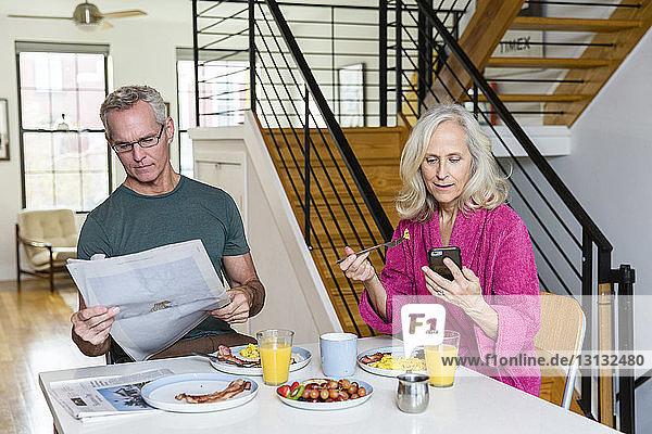 Mann liest Zeitung  während die Frau ein Smartphone am Esstisch benutzt
