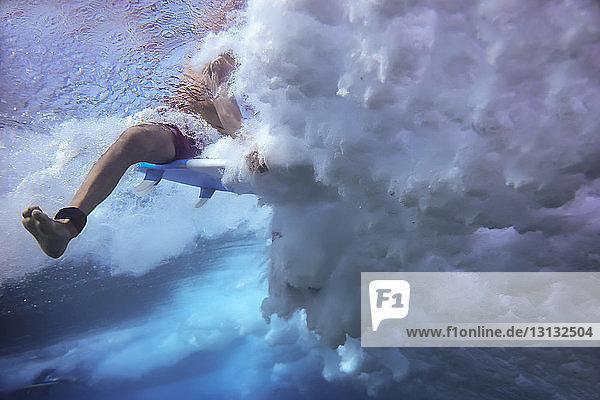 Niedrigwinkel-Zuschnittbild eines Mannes  der im Meer unter Wasser surft Niedrigwinkel-Zuschnittbild eines Mannes, der im Meer unter Wasser surft