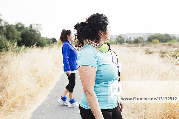 Side view of friends looking away while exercising on road against clear sky