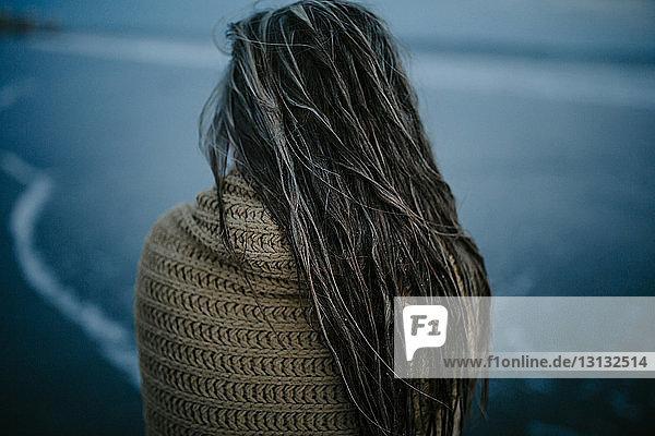 Rückansicht einer nassen Frau mit Schal  die in der Abenddämmerung am Strand steht