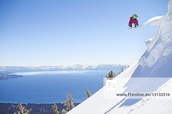 Snowboarder jumping from snowcapped mountain against clear sky