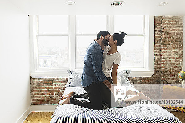 Romantic couple kissing while kneeling on bed at home