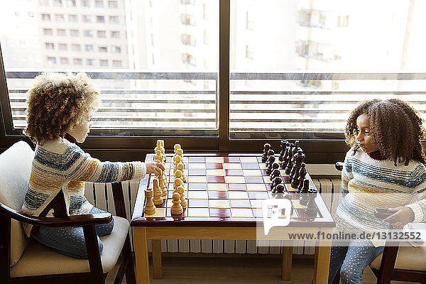 Sisters playing chess on table at home