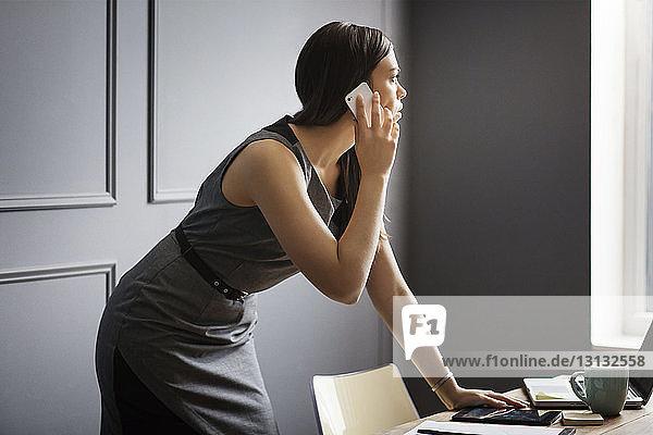 Geschäftsfrau mit Smartphone bei der Arbeit im Büro