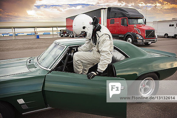 Sportsman sitting in vintage car while preparing for sports race