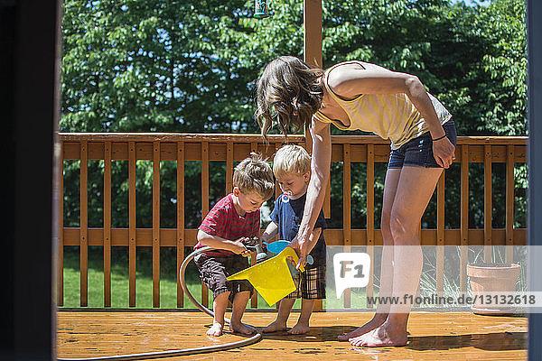 Kinder gießen Wasser in einen Behälter  der von der Mutter auf der Veranda gehalten wird  durch die Tür gesehen