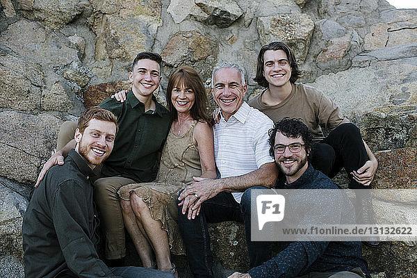 Porträt von glücklichen Eltern mit Söhnen  die im Park vor Felsformationen sitzen