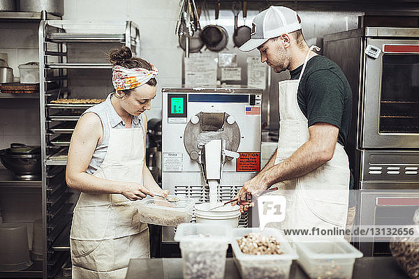 Colleagues using machinery while making ice cream