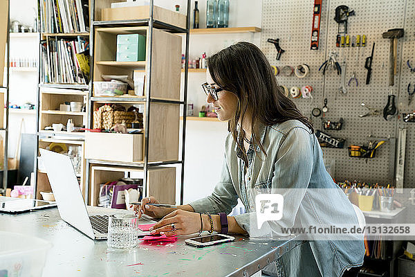 Side view of businesswoman working on laptop computer in office