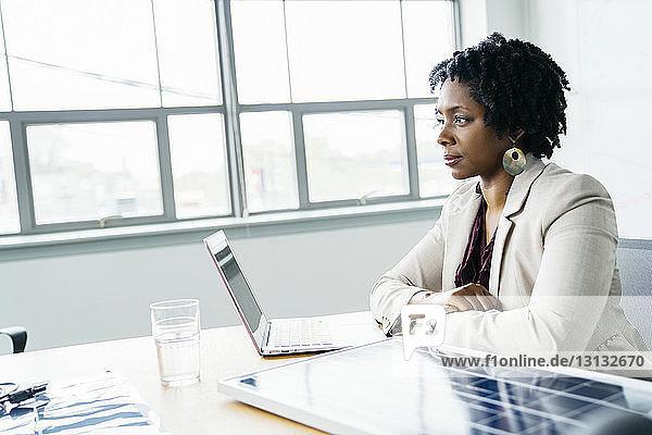 Nachdenkliche Geschäftsfrau sitzt am Modell eines Solarpanels auf dem Tisch