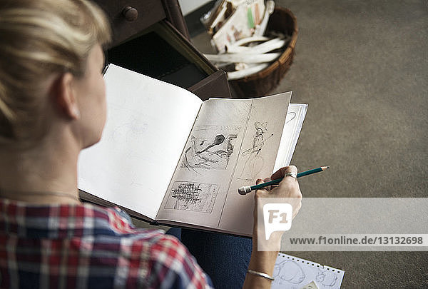 Female artist looking at sketches in book while sitting at home