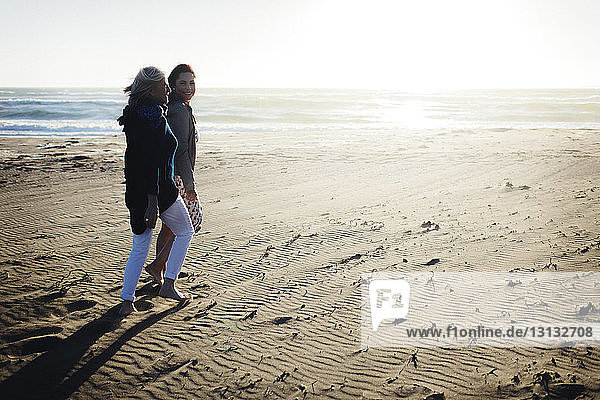 Mother and daughter walking at beach against clear sky during sunny day