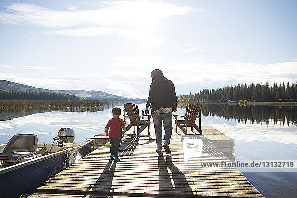 Rear view of mother and son walking on wooden pier over lake against sky