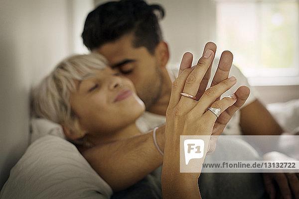 Zärtlicher junger Mann küsst Frau  während er im Schlafzimmer die Hand hält