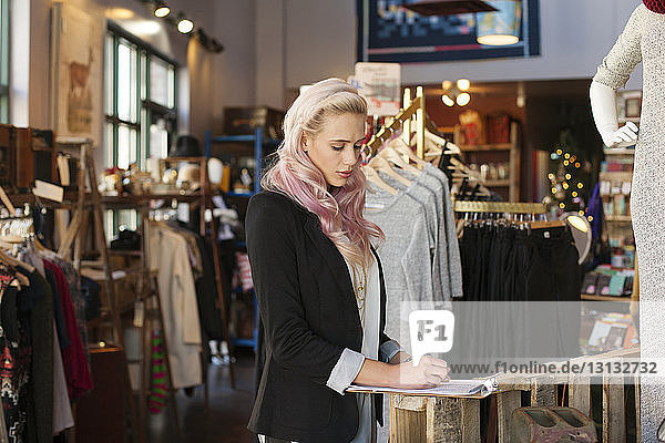 Young female owner writing on clipboard in clothing store