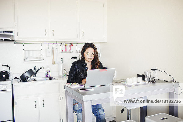 Businesswoman using laptop computer in home office