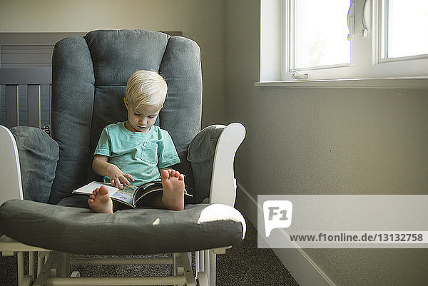 Boy reading book while sitting on chair at home