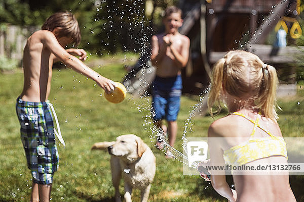 Rear view of girl spraying water on dog and friends at backyard