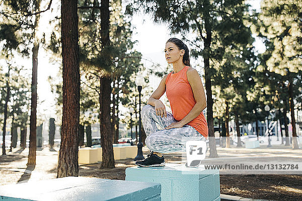 Thoughtful female athlete crouching on small blue column at park