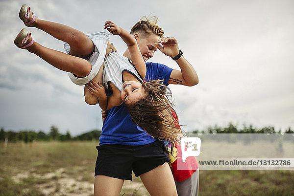 Fröhliche Geschwister spielen im Park gegen bewölkten Himmel