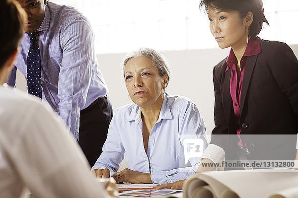 Business people looking at colleague during meeting in office