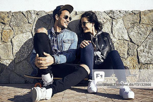 Glückliches Paar unterhält sich  während es auf einem Skateboard an einer Steinmauer sitzt