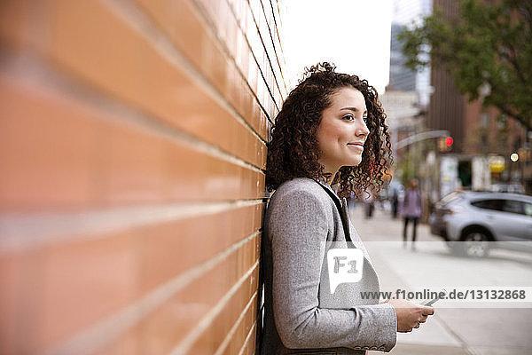 Seitenansicht einer nachdenklichen Geschäftsfrau  die ein Smartphone in der Hand hält  während sie an einer Ziegelmauer steht